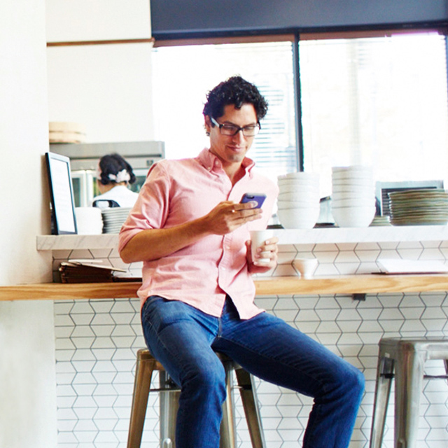 Man seated at café counter checking his phone.